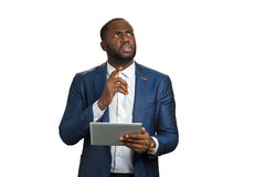 Thoughtful black manager on white background. Businessman raised his index finger up. black businessman worriedly thinking with computer tablet. Businessman stock photo