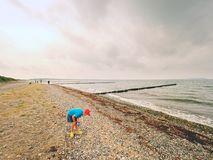 A thoughtful blond boy staying on beach near water. Long stony beach with wooden breakwater. To protect a coast from the force of sea waves Royalty Free Stock Photos