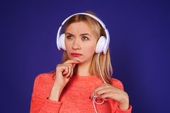 Thoughtful blond in headphones. On violet Stock Photography