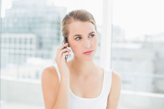 Thoughtful blond woman on the phone Stock Images