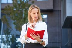 Thoughtful blonde business woman with notebook against of office building royalty free stock photography