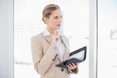 Thoughtful blonde businesswoman holding datebook. In bright office Royalty Free Stock Image