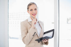 Thoughtful blonde businesswoman holding datebook standing Royalty Free Stock Photos