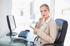Thoughtful blonde businesswoman texting. Thoughtful blonde businesswoman in bright office texting Stock Photo
