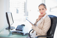 Thoughtful blonde businesswoman using tablet. Thoughtful blonde businesswoman in bright office using tablet Stock Image