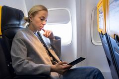 Woman reading on digital e-reader while traveling by airplane. stock photos