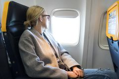 Thoughtful woman looking through the window while traveling by airplane. royalty free stock images