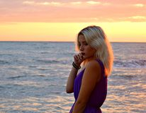Thoughtful blonde girl on the sea at sunset Stock Photography