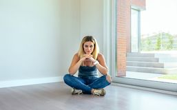 Thoughtful girl sitting in a living room. Thoughtful blonde girl sitting in a empty living room royalty free stock images