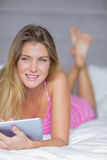 Thoughtful blonde lying on her bed using her tablet pc Stock Images