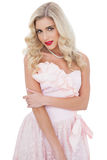Thoughtful blonde model in pink dress posing holding her arm Stock Images