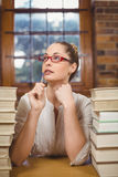 Thoughtful blonde teacher sitting between books in the library Royalty Free Stock Photo