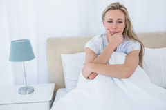 Thoughtful blonde under duvet in bed Royalty Free Stock Images