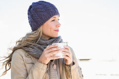 Thoughtful blonde in warm clothes holding hot beverage Stock Photography