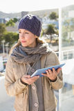 Thoughtful blonde in warm clothes using tablet Royalty Free Stock Image