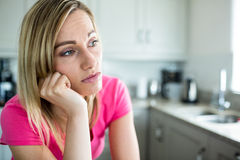 Thoughtful blonde woman leaning on her counter Stock Image