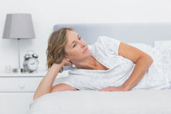 Thoughtful blonde woman lying on bed Royalty Free Stock Image