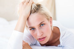 Thoughtful blonde woman lying on the bed Stock Image