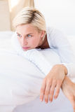 Thoughtful blonde woman lying on the bed Stock Photography