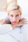 Thoughtful blonde woman lying on the bed Stock Photos