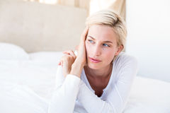Thoughtful blonde woman lying on the bed Royalty Free Stock Photos