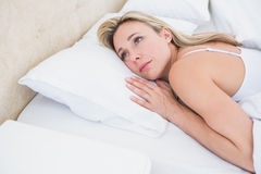Thoughtful blonde woman lying in bed Royalty Free Stock Photography