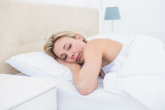 Thoughtful blonde woman lying in bed Stock Image