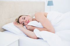 Thoughtful blonde woman lying in bed Stock Photo
