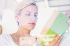 Thoughtful blonde woman reading a book Stock Image