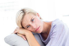Thoughtful blonde woman sitting on the couch Stock Images