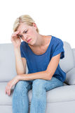 Thoughtful blonde woman sitting on the couch. On white background Stock Photography
