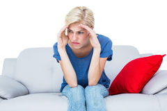 Thoughtful blonde woman sitting on the couch. On white background Stock Images