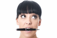 Thoughtful Bored Confused Attractive Young Woman with Pen in Mouth stock photo