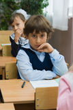 Thoughtful boy. Children at school at a lesson. The thoughtful boy sits at a school desk Stock Photo