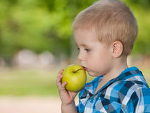 Thoughtful boy with an apple Royalty Free Stock Photos