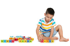 Thoughtful boy with blocks on the floor Stock Photos