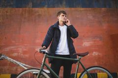 Thoughtful boy with brown hair standing with bicycle and dreamily looking aside talking on his cellphone. Young man in. Thoughtful boy with brown hair standing Stock Images