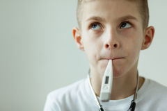 Thoughtful Boy with Digital Thermometer in Mouth Royalty Free Stock Images