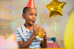 Thoughtful boy drinking juice during birthday party. At home royalty free stock photography