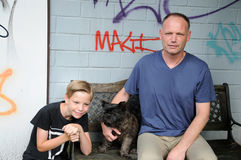 Thoughtful boy. Father son and dog sitting in their garden in front of their graffiti wall stock photo