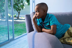 Thoughtful boy looking away while sitting on sofa. At home Royalty Free Stock Photos