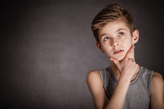 Thoughtful Boy Looking Up on Gray with Copy Space Royalty Free Stock Photo