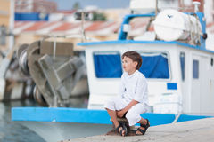 Thoughtful boy looks at ship at sea and dreams Royalty Free Stock Image