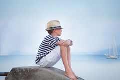 Thoughtful boy looks at ship at sea and dreams Royalty Free Stock Images