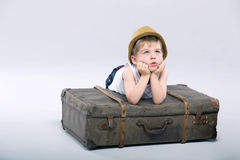 Thoughtful boy lying on the suitcase Royalty Free Stock Images