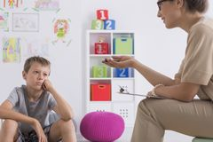 Thoughtful boy during meeting with psychotherapist Royalty Free Stock Photo