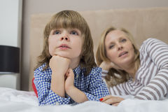 Thoughtful boy with mother in bed Stock Photos