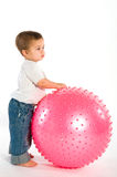 Thoughtful boy with pink fitness ball Royalty Free Stock Photos