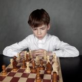 Thoughtful boy playing chess, studio Stock Image