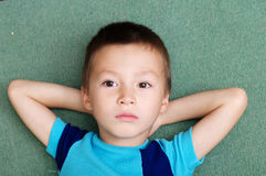 Thoughtful boy portrait lying on crossed arms royalty free stock image